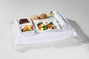 Serviertablett mit Käseravioli, Beilagensalat und Dessert